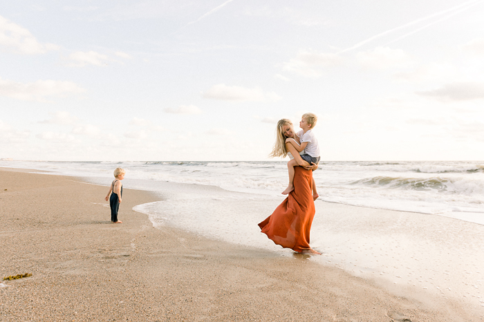 mom wearing long skirt, with two sons, on beach at sunrise