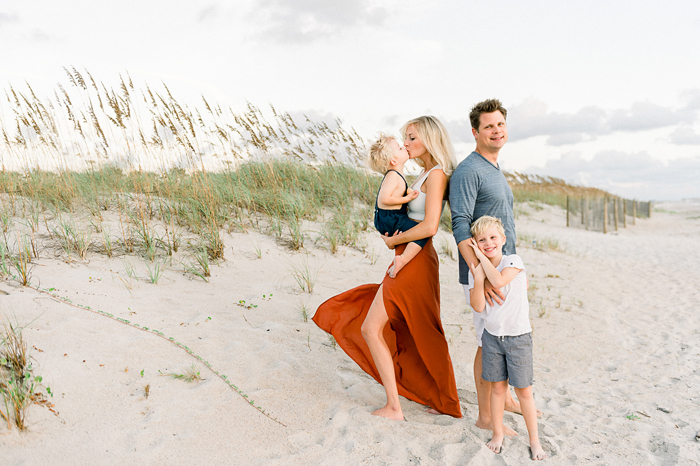 blonde mom kissing son with dad and son smiling on beach
