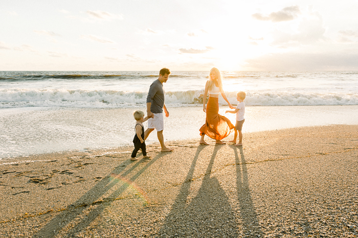 family of four on beach at sunrise with long shadows and lens flare
