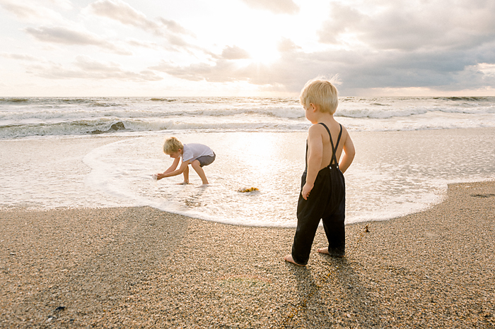 two blonde boys playing on Florida beach at sunrise