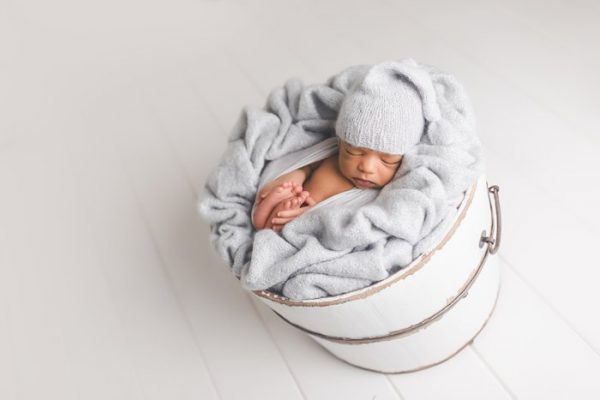 newborn baby in white bucket