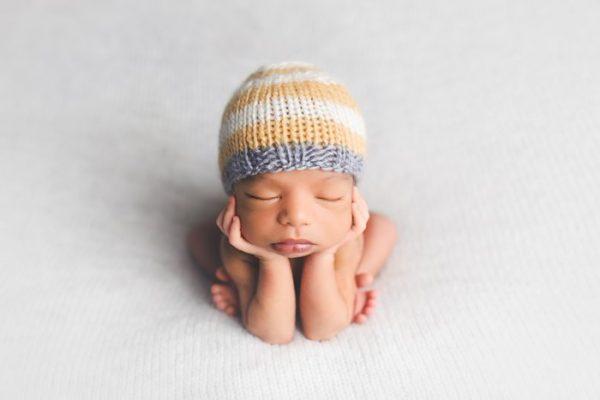 newborn baby wearing yellow striped knit hat