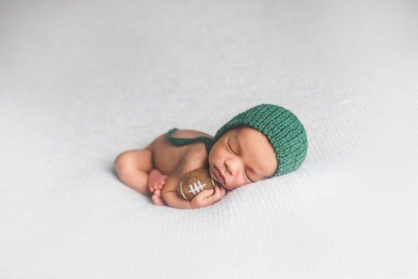 newborn baby wearing knit green bonnet, cradling plush football