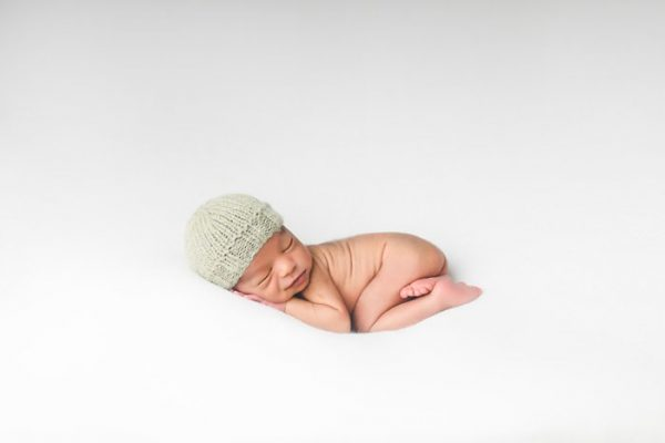 newborn baby wearing knit gray skull cap