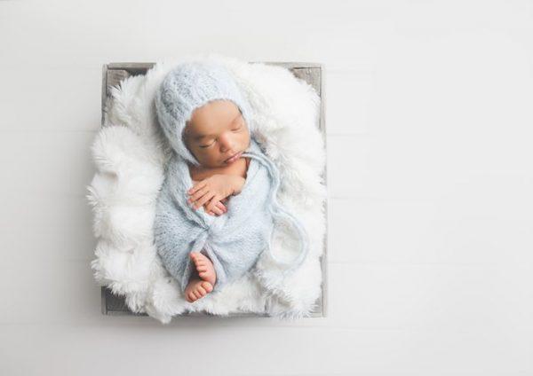 newborn baby on white fluff, in gray blanket