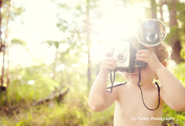 baby photography using a vintage camera as a prop and sunflare