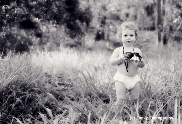photograph of a toddler with a vintage starflex kodak camera in the woods