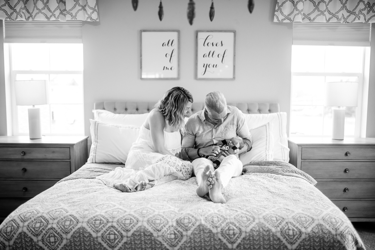 black and white image of mother and father with newborn