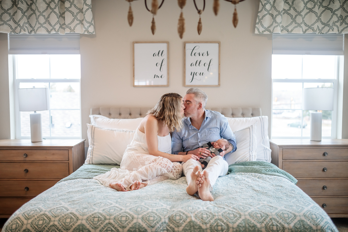 mother and father kissing, holding newborn in lap