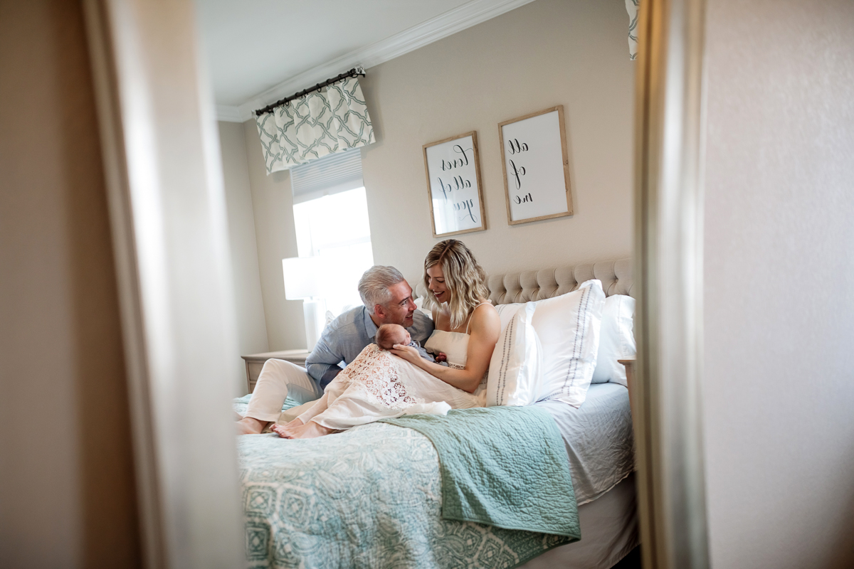 mother and father with newborn, reflected in bedroom mirror