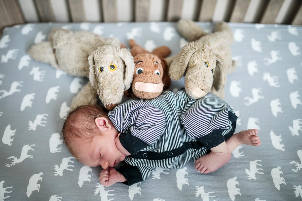 newborn baby boy wearing striped sleeper, asleep in crib with stuffies
