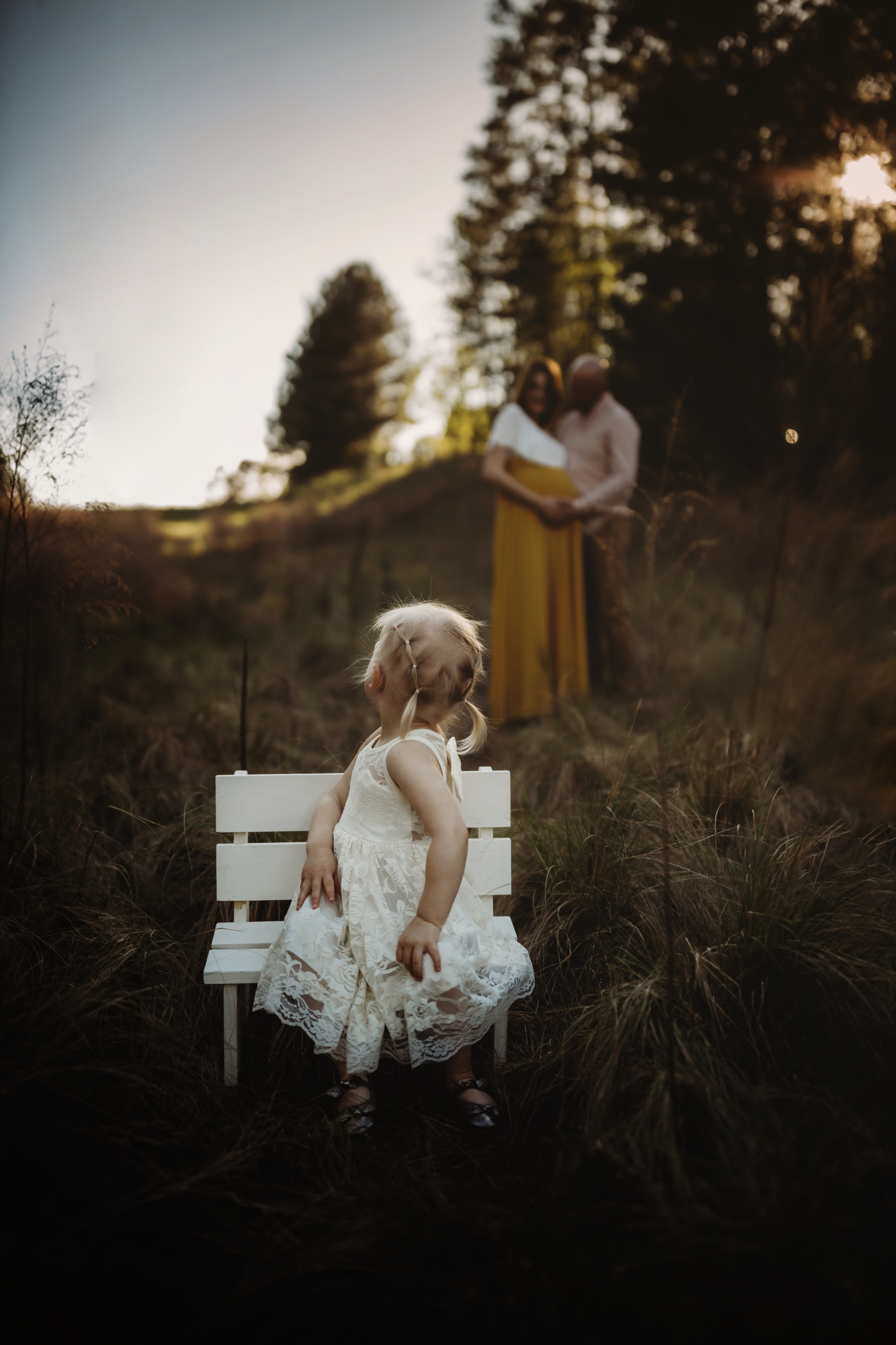 little girl on bench in foreground, parents in background, twins maternity photography