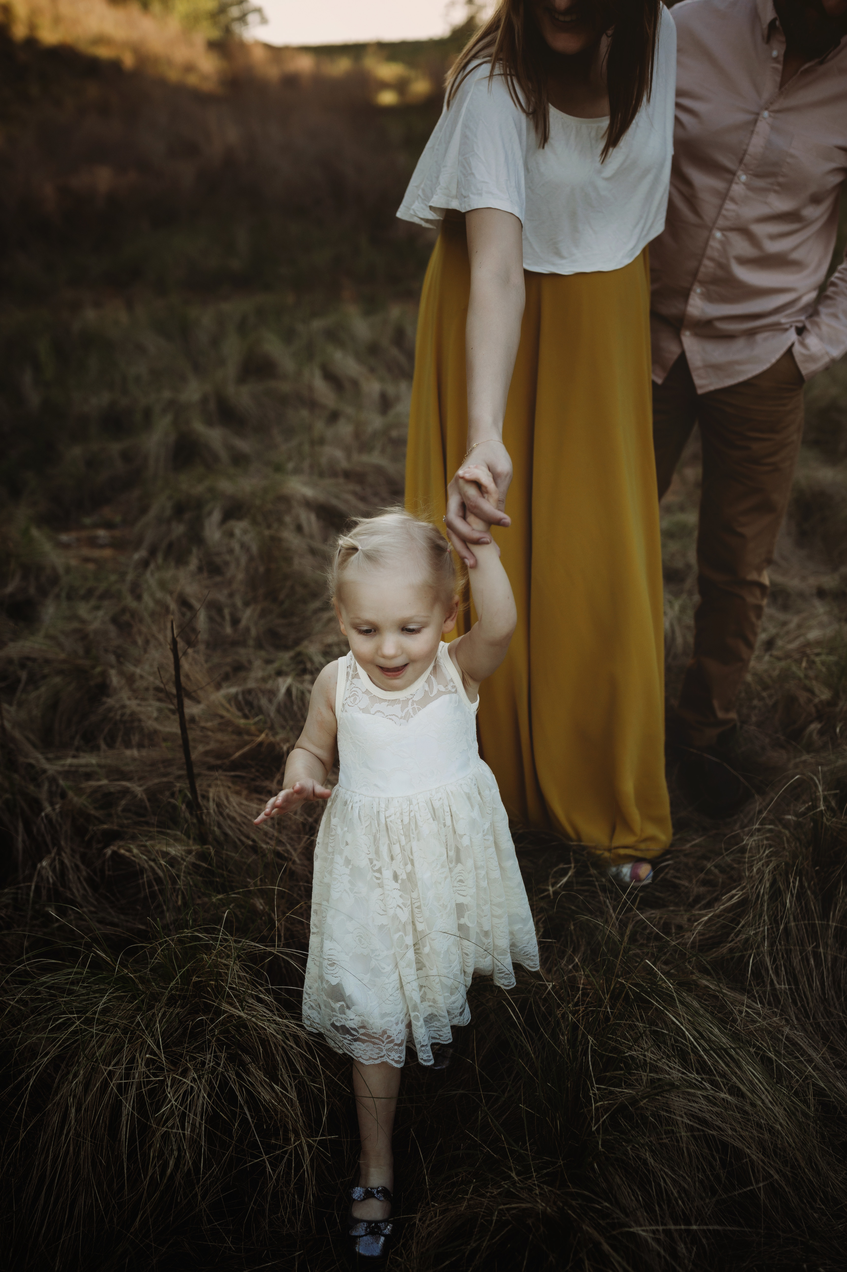 little girl in white dress in foreground, holding mother's hand, twins maternity photography